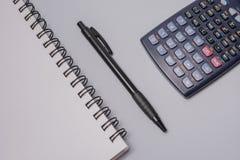 Calculadora, caderno e pena na tabela do escritório no fundo branco Conceito do orçamento Fotografia de Stock Royalty Free