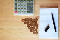 Calculadora, caderno vazio, pena e moedas imagens de stock