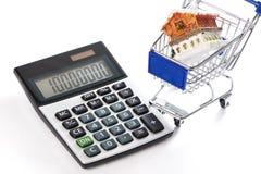 Calculadora, carretilla que hace compras y casa aisladas Foto de archivo libre de regalías