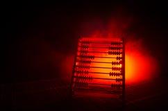 Calculadora chinesa com os grânulos coloridos no fundo alaranjado da obscuridade do fumo do fogo Foto do negócio, criança do conc Imagem de Stock