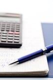 Calculadora científica, una pluma de la azul-plata en el libro de trabajo de los marhs Foto de archivo