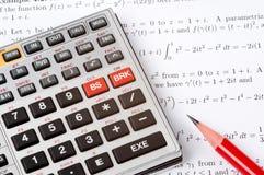 Calculadora científica al lado de la matemáticas Foto de archivo libre de regalías