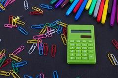 Calculadora, clips de papel, marcadores en tablero negro Imagen de archivo