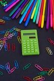 Calculadora, clips de papel, marcadores en tablero negro Foto de archivo