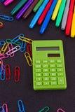 Calculadora, clips de papel, marcadores en tablero negro Fotografía de archivo libre de regalías