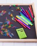 Calculadora, clips de papel, marcadores en tablero negro Fotografía de archivo