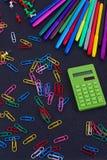 Calculadora, clips de papel, marcadores en tablero negro Imagenes de archivo