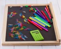 Calculadora, clips de papel, marcadores en tablero negro Imágenes de archivo libres de regalías