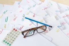 A calculadora com espetáculos pôs sobre a pilha de papel da sobrecarga Fotografia de Stock Royalty Free