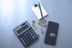 Calculadora com telefone e moedas fotografia de stock royalty free