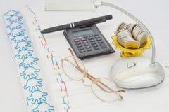 Calculadora com vidros e moedas na bandeja do ouro com suporte Foto de Stock Royalty Free