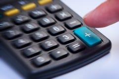 Calculadora con el botón más. Imagenes de archivo