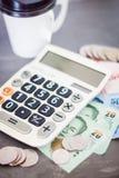 Calculadora con el dinero en fondo gris Foto de archivo libre de regalías