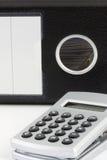 Calculadora con el expediente negro en el fondo imagen de archivo libre de regalías