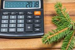 Calculadora con el número 2018 y rama Spruce en la tabla de madera Cierre para arriba Fotos de archivo