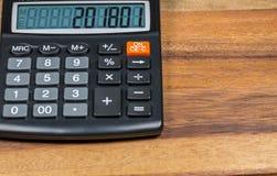 Calculadora con la fecha del Año Nuevo en la exhibición en la tabla de madera Fotografía de archivo libre de regalías