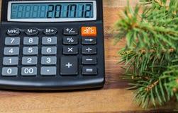 Calculadora con la fecha del Año Nuevo en la exhibición y la rama de árbol spruce en la tabla de madera Fotografía de archivo