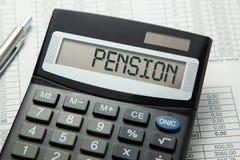 Calculadora con la inscripción en la exhibición de la PENSIÓN en las tablas de papel Cálculo de la pensión fotos de archivo libres de regalías