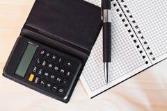 Calculadora con la libreta y la pluma Foto de archivo