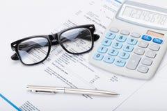 Calculadora con la pluma, los vidrios y la factura de servicios públicos bajo ella Foto de archivo libre de regalías