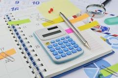 Calculadora con las notas de post-it coloridas sobre la página del diario del negocio Fotografía de archivo