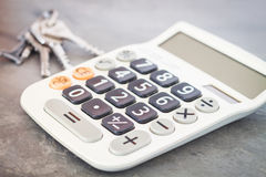 Calculadora con llaves en fondo gris Foto de archivo libre de regalías