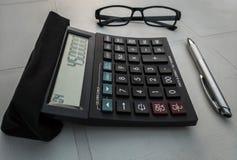 Calculadora con un par de vidrios y de una pluma imagenes de archivo