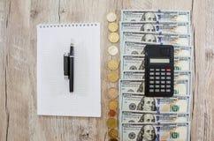 Calculadora, cuaderno, dólares y monedas Cientos billetes de dólar y monedas en fila en la tabla Visi?n desde arriba imagenes de archivo