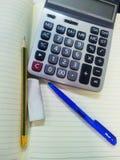 Calculadora, cuaderno, pluma Imagen de archivo libre de regalías