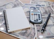 Calculadora, cuaderno y lápiz en moneda de los yenes japoneses Imagen de archivo