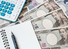 Calculadora, cuaderno y lápiz en moneda de los yenes japoneses Fotos de archivo