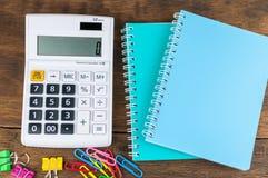 Calculadora, cuadernos y clips en fondo de madera Fotos de archivo