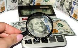 Calculadora, dólares americanos, lupa y mano femenina en el fondo blanco fotos de archivo
