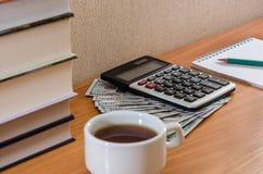 Calculadora, dólares, libreta y libros en la tabla fotos de archivo