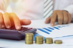 calculadora da imprensa do homem de negócios e gráfico de negócio da verificação no papel w foto de stock