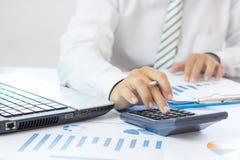 calculadora da imprensa do homem de negócios e gráfico de negócio da verificação no papel w imagens de stock