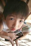 Calculadora da terra arrendada do menino que olha acima Fotografia de Stock