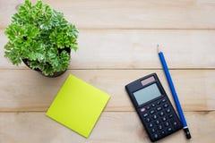 A calculadora da vista superior, a nota de post-it, o lápis e alguma planta puseram sobre o wo Foto de Stock Royalty Free