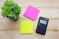 A calculadora da vista superior, a nota de post-it, o lápis e alguma planta puseram sobre o wo Imagem de Stock Royalty Free