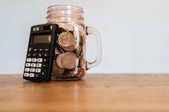 Calculadora de bolsillo negra al lado del tarro de albañil por completo de monedas imágenes de archivo libres de regalías