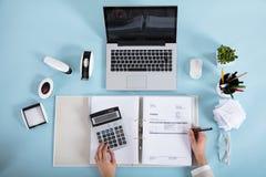 Calculadora de Calculating Invoice Using de la empresaria fotografía de archivo libre de regalías