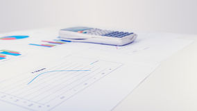 Calculadora de escritorio al lado de diversos diagramas Imágenes de archivo libres de regalías