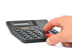 Calculadora de escritorio con el primer masculino de la mano Foto de archivo