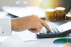 calculadora de la prensa del hombre de negocios y gráfico de negocio del control en el papel w Fotografía de archivo