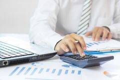calculadora de la prensa del hombre de negocios y gráfico de negocio del control en el papel w Imagenes de archivo