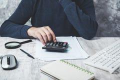 Calculadora de mão do homem no documento foto de stock
