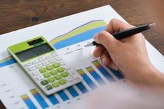 Calculadora de Person Hands With Graph And Imagens de Stock