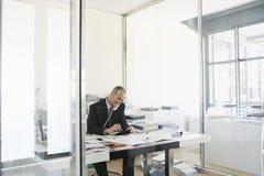 Calculadora de Using Telephone And del hombre de negocios en el escritorio Imagen de archivo