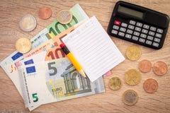 Calculadora, dinero, lápiz y lista de compras fotografía de archivo