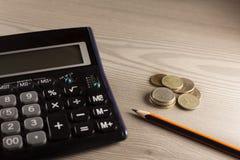 Calculadora, dinero y lápiz Foto de archivo
